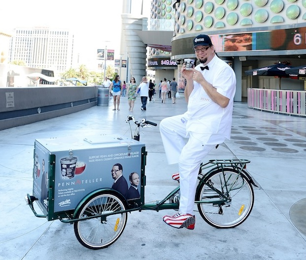 penn jillette sits on a pedal cart with walgreens ice cream